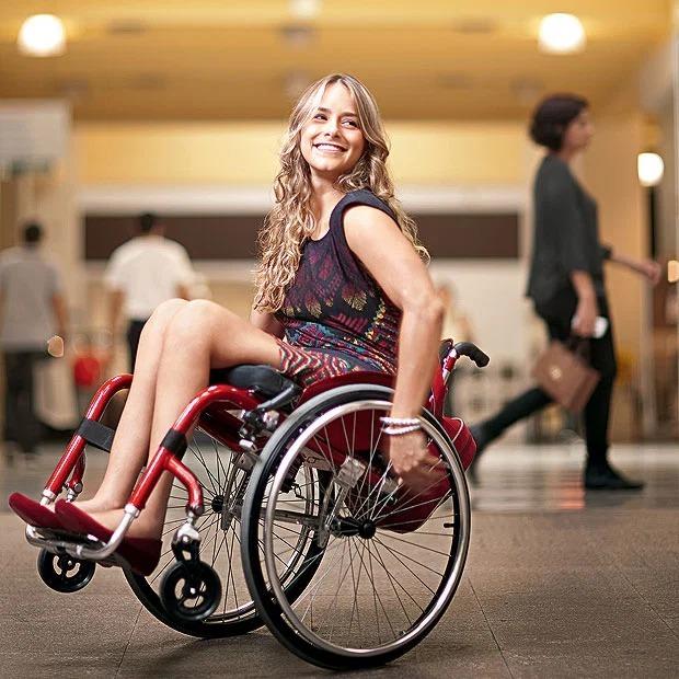 Tabata sorri sentada em cadeira de rodas vermelha. Fim da descrição.