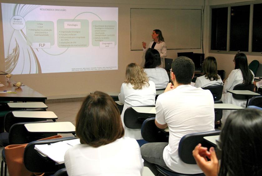 Em sala de aula, estudantes sentados em carteiras observam professora, que realiza apresentação em projeção. Fim da descrição.
