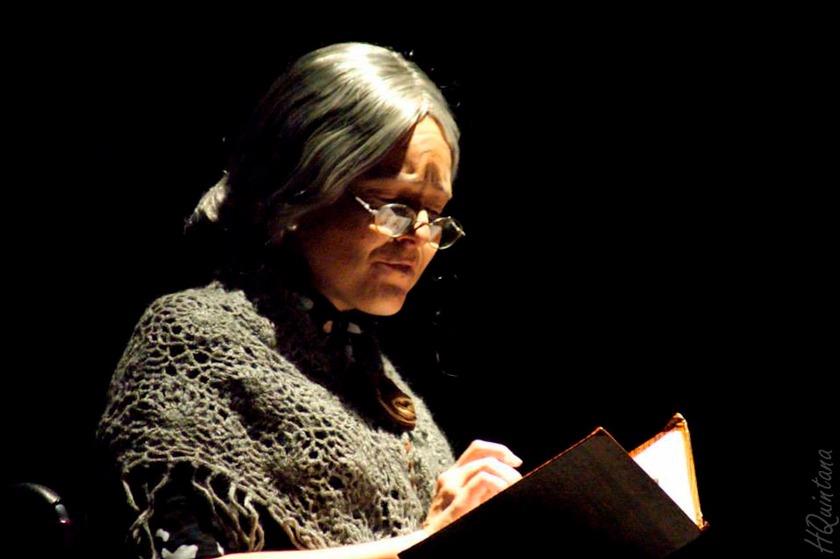 Em peça, Vanessa, usando peruca de cabelo grisalho, óculos e blusa de lã, olha para livro que está em suas mãos. Fim da descrição.