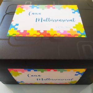 Caixa preta com papel na tampa e na lateral, escrito 'Caixa multissensorial'. O papel possui desenhos de quebra-cabeças coloridos em sua borda. Fim da descrição.