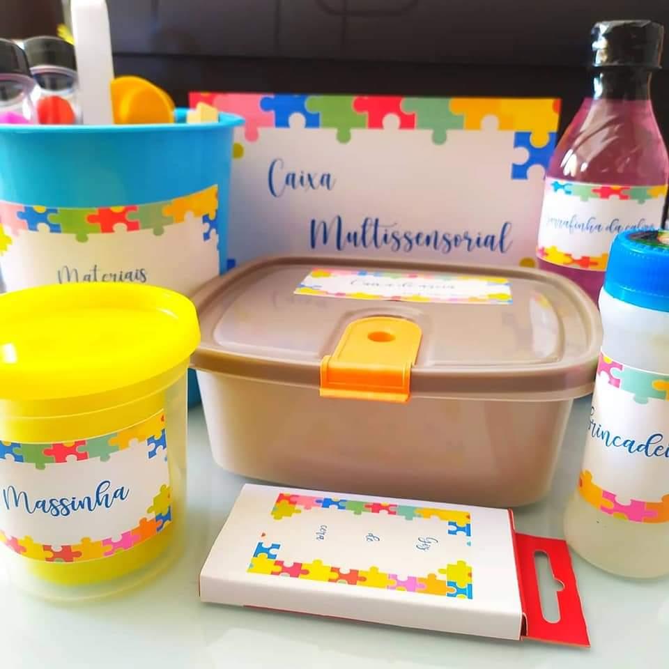 Sobre mesa, materiais da caixa multissensorial, como caixa de giz de cera, massinha, garrafas, pote e baldinho coloridos. Cada item possui uma etiqueta com sua descrição. Fim da descrição.