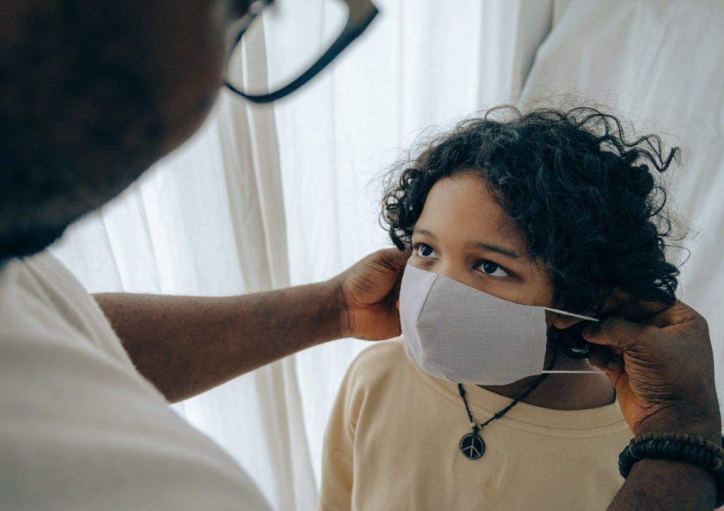 Em frente à cortina branca, pai coloca máscara de proteção contra a covid-19 em rosto de menina. Fim da descrição.