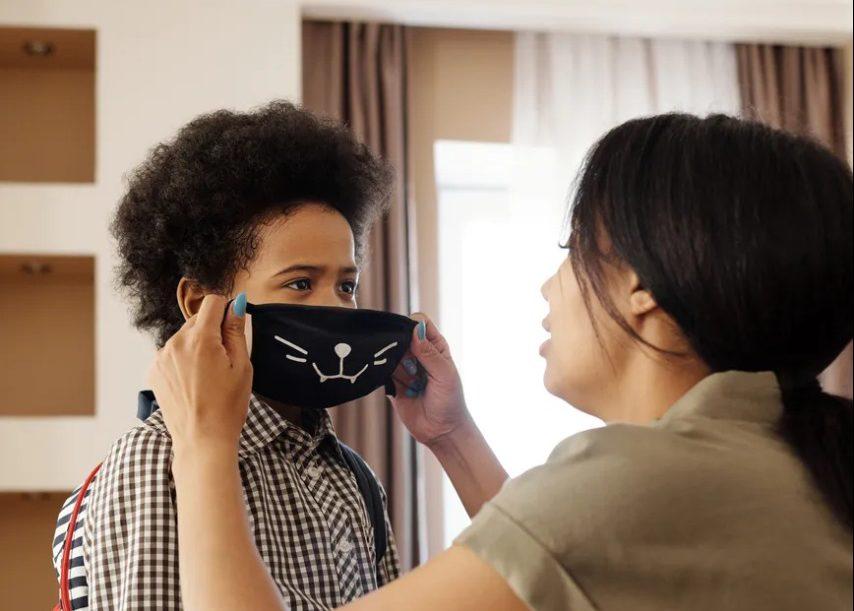 Mulher coloca máscara de proteção contra a covid-19 e rosto de criança. Fim da descrição.