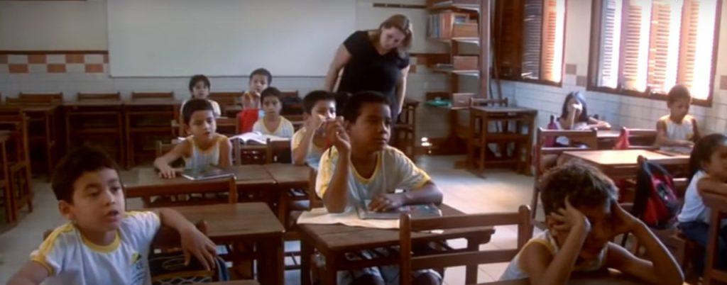 Em sala de aula, estudantes olham atentos para frente sentados em cadeiras escolares de madeira. Ao fundo educadora em pé observa caderno de um dos estudantes. Fim da descrição.