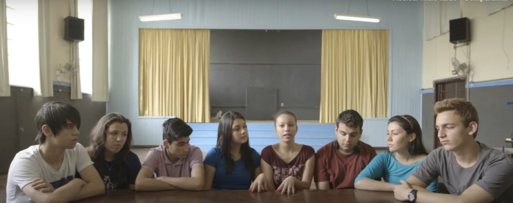 Ao redor de uma mesa, oito estudantes adolescentes  estão sentados lado a lado em semicírculo. Ao fundo, cenário de um palco, com caixa de som e cortinas. Fim da descrição.