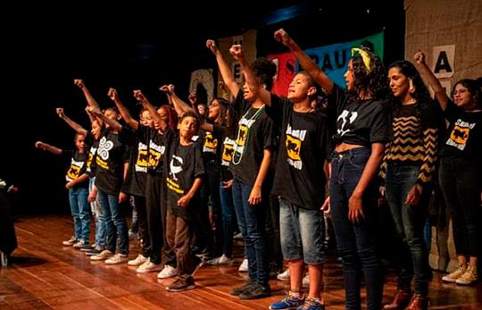"""Em auditório, estudantes cerram punhos para o alto. Eles vestem camisetas pretas com as palavras """"Sarau: herança afro"""". Ao fundo, há obras artísticas em conjunto com a palavra """"Sarau"""". Fim da descrição."""