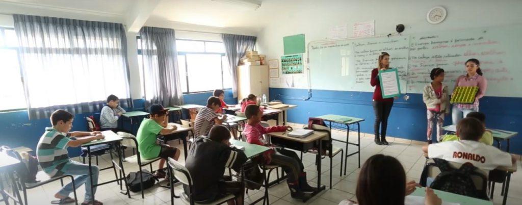 Em sala de aula, duas estudantes em pé, em frente à lousa, apresentam materiais para os demais alunos. Ao lado, educadora segura um cartaz. Fim da descrição.