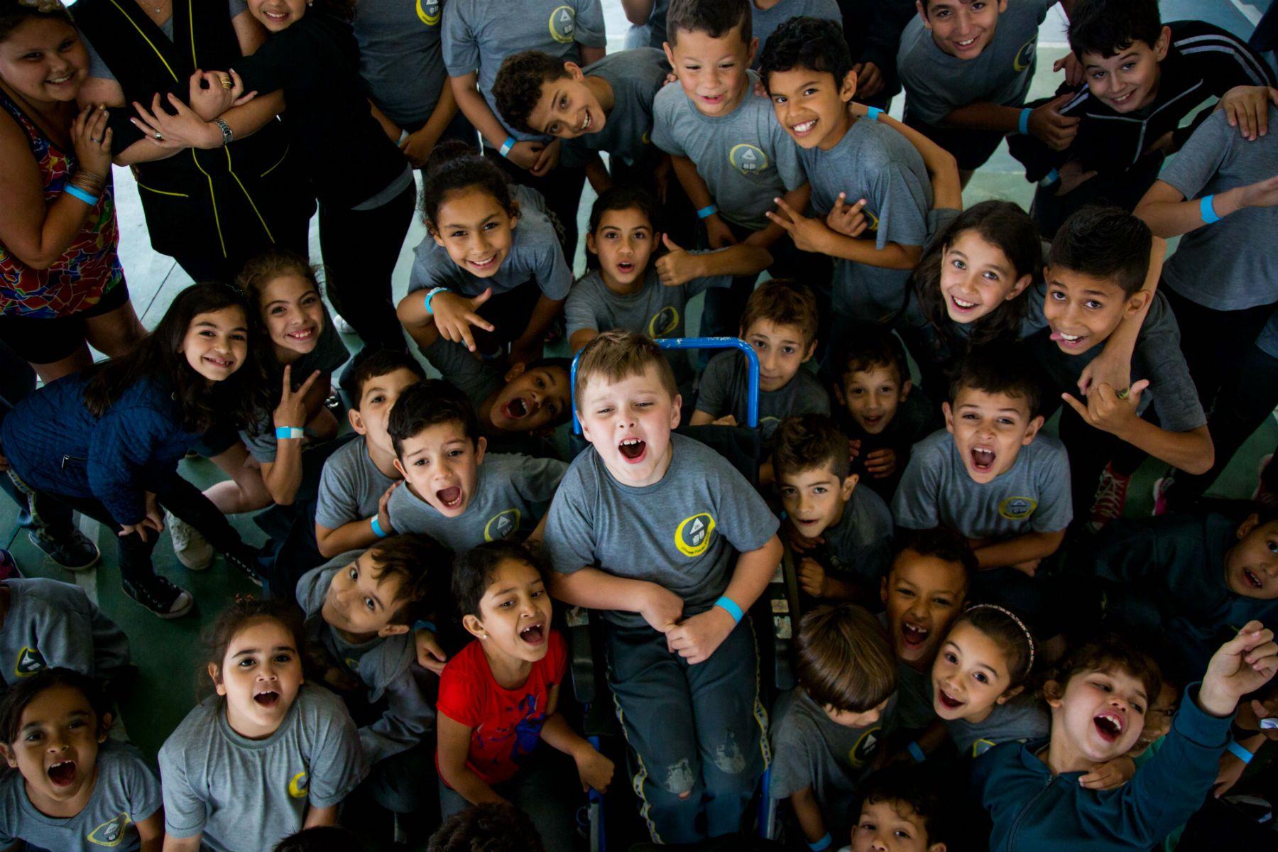 Vistos de cima, meninas e meninos uniformizados posam para foto, sorrindo. Ao centro, há uma criança com cadeira de rodas