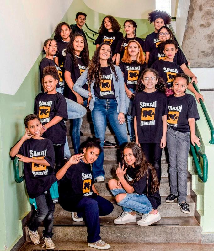 """Em escadaria da escola, educadora Lidiane posa para foto com seus estudantes. Há duas meninas agachadas nos degraus da frente e os demais estão em pé, em volta da professora. Todos sorriem e usam camisetas pretas escrito """"Sarau Heranças Afro"""". Fim da descrição."""