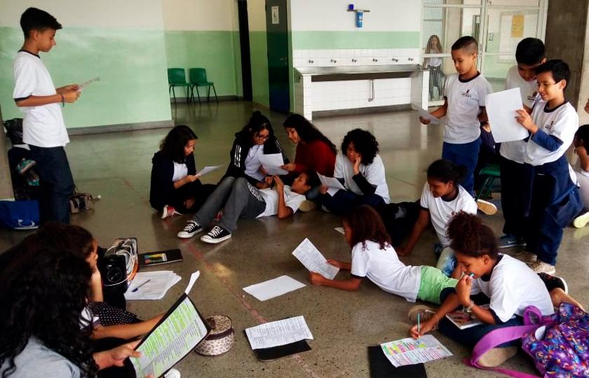 Em pátio escolar, próximo a bebedouro, estudantes se reúnem em roda. Alguns estão sentados no chão e seguram papel com poemas nas mãos. Fim da descrição.