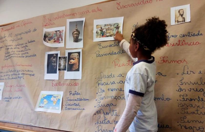 Estudante uniformizada aponta para imagem impressa e colada em mural feito de papel pardo que cobre toda a lousa da sala de aula. Há textos escritos com canetão vermelho e azul e outras imagens relacionadas à cultura afro coladas. Fim da descrição.