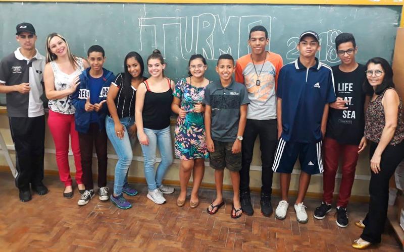 """Em sala de aula e em frente à lousa, nove estudantes posam para fotos ao lado de educadores. Na lousa está escrito om giz """"Turma 2018"""". Fim da descrição."""