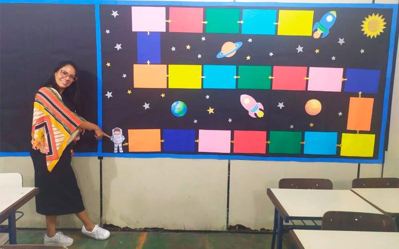 Em sala de aula, educadora Vilma Soares posa para foto ao lado de jogo de trilha de objetos espaciais.