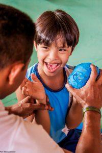 Estudante com síndrome de down dá risada enquanto educador coloca em sua mão uma bola azul. Fim da descrição.