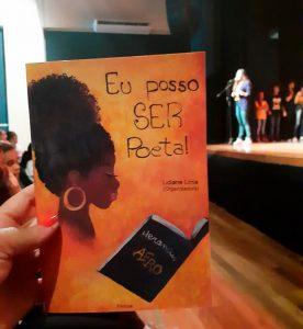 """Educadora segura livro. A capa é laranja, com ilustração de mulher negra de perfil e de um livro preto aberto, escrito """"heranças afro""""; textos """"Eu posso ser poeta!"""" e """"Lidiane Pereira (organizadora"""". Ao fundo, palco com alguém de pé se apresentando e outras pessoas assistindo. Fim da descrição."""