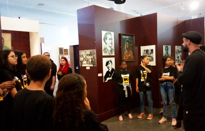 Em sala do Museu Afro-Brasil, estudantes se reúnem em roda em frente à exposições com rostos de figuras importantes para o movimento negro, enquanto guia fala. Fim da descrição.
