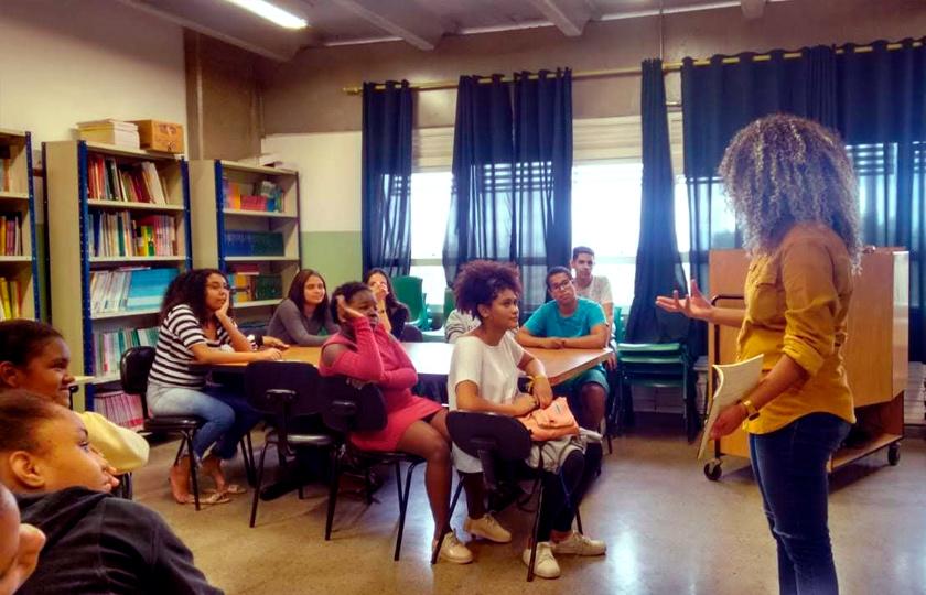 Em sala de leitura, estudantes sentados em cadeiras observam mulher em pé. fim da descrição.