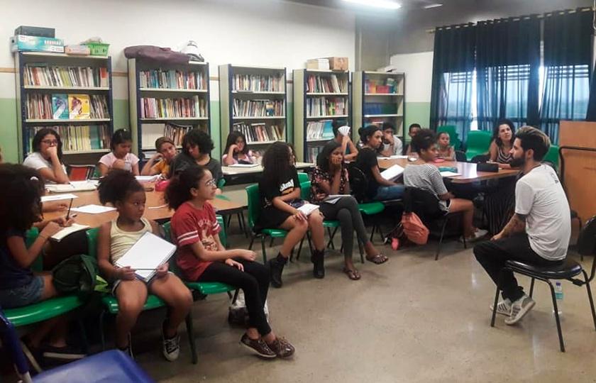 Em espaço de biblioteca, estudantes se reúnem em roda sentados em cadeiras. Ao centro, uma homem negro fala aos alunos. Fim da descrição