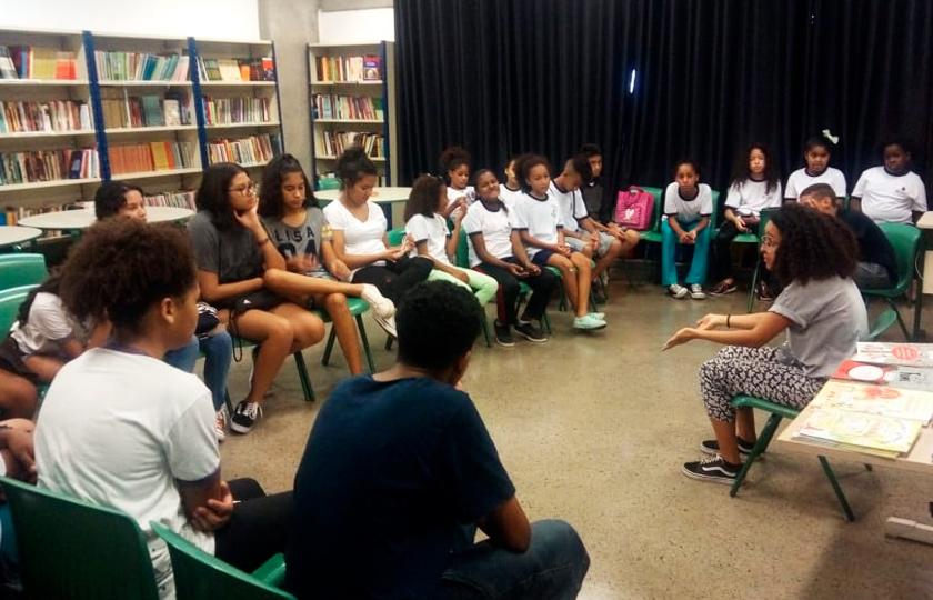 Em espaço de biblioteca, estudantes se reúnem em roda sentados em cadeiras. Ao centro, uma mulher negra de cabelos cacheados fala aos alunos.