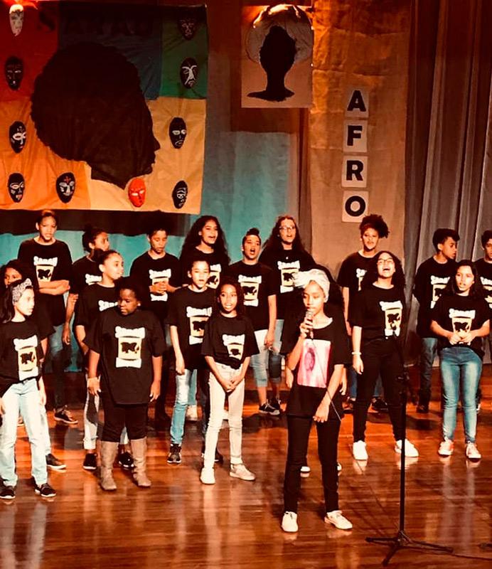 """Em auditório, estudantes vestindo camisetas pretas se reúnem para realização de sarau. Ao fundo há obras artísticas em conjunto com a palavra """"Afro"""". Fim da descrição."""