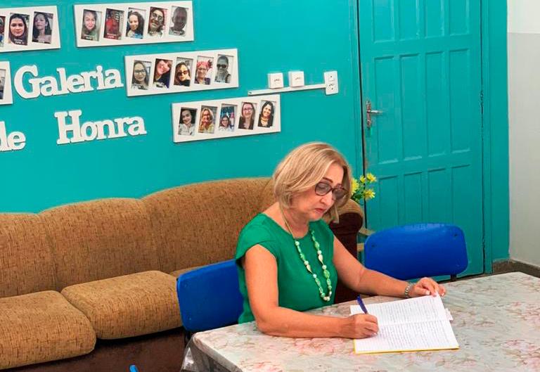Sentada à mesa na diretoria, gestora Lucia Cristina escreve em papéis. Fim da descrição.