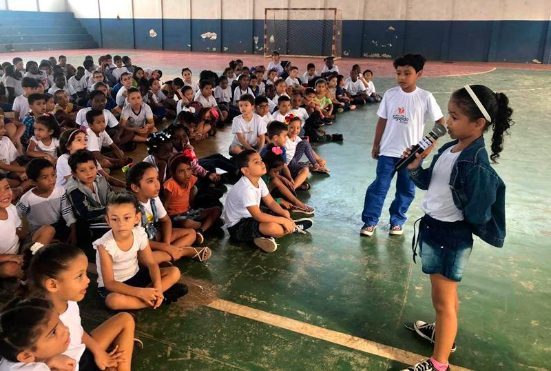 Em quadra esportiva, dezenas de estudantes estão sentados no chão. Um menino e uma menina estão à frente deles, em pé, e a menina fala ao microfone. Fim da descrição.