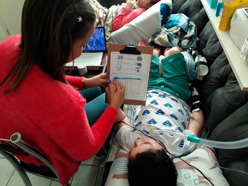 Em sala de estar, educadora segura prancheta com atividade para aluno que está deitado no sofá e utiliza aparelho médico conectado ao seu tórax. Fim da descrição.