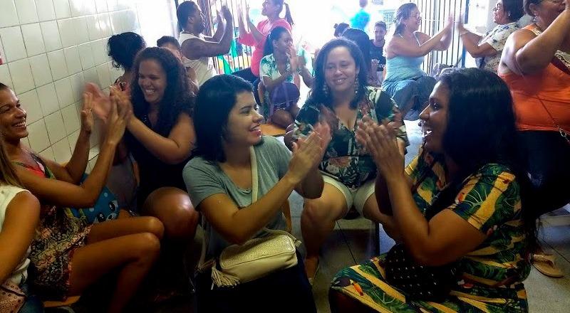 Em pátio escolar, mães de alunos estão sentadas em cadeira e batem palmas. Fim da descrição.