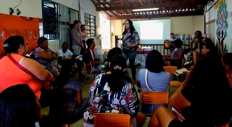 Em pátio escolar, coordenadora Mirtes, em pé, fala com familiares de alunos sentadas em cadeiras. Fim da descrição.