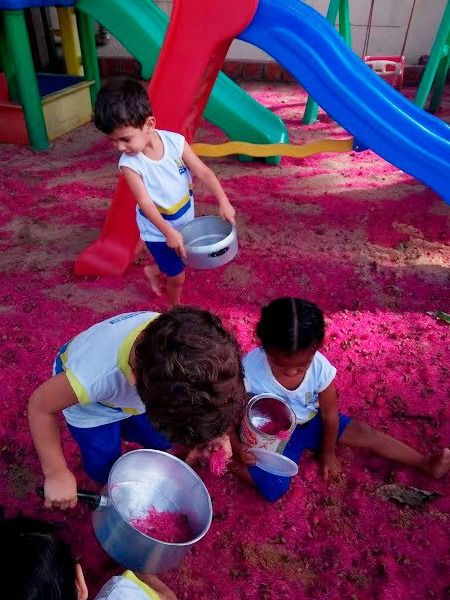 Em parquinho de escola, três crianças uniformizadas brincam depositando flores rosas do jambeiro em panelas. Fim da descrição.