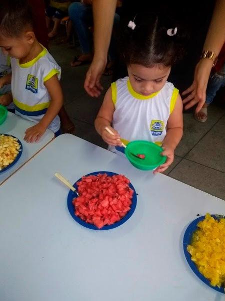 Criança segurando pratinho e colher pega melancia de prato depositado sobre mesa de refeição. Fim da descrição.