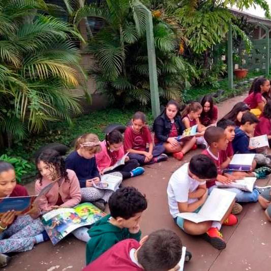 Em área externa, crianças estão sentadas no chão lendo livros. Fim da descrição.