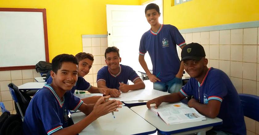 Em sala de aula, cinco estudantes uniformizados sorriem para a foto. Quatro deles estão sentados à mesa e um está de pé ao lado dos colegas. Há um livro sobre a mesa. Fim da descrição.