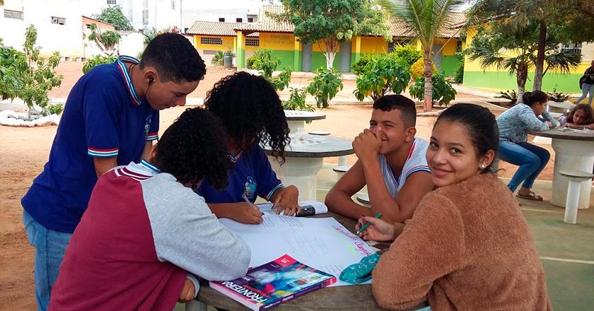 Em pátio escolar, cinco estudantes estão ao redor de mesa, estudante. Dois deles sorriem para a foto. Fim da descrição.