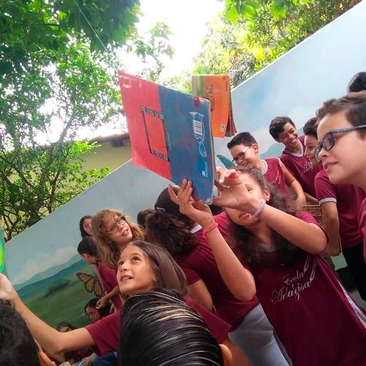 Dezenas de estudantes em pátio escolar. Duas meninas pegam livros da árvore enquanto menino observa. Fim da descrição.