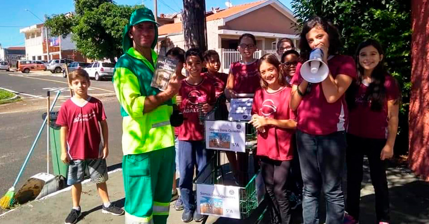 Estudantes uniformizados acompanham educadora em entrega de livros nas ruas. Coletor de lixo sorri para a foto, segurando um livro. A educadora está segurando um megafone e, ao lado dela, as crianças levam um carrinho com livros. Fim da descrição.