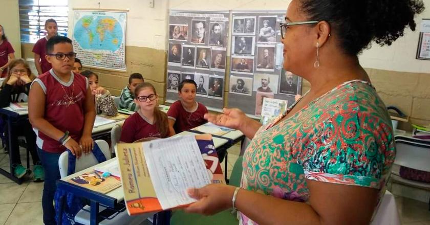 Em sala de aula, mulher está de frente para estudantes. Ela sorri e segura livro em uma das mãos. Fim da descrição.
