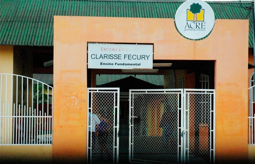 Fachada da Escola Estadual Clarisse Fecury. Letreiro com o nome da escola está fixado em estrutura laranja acima de portão com grades brancas. Acima, telhado está pintado na cor verde. Fim da descrição.