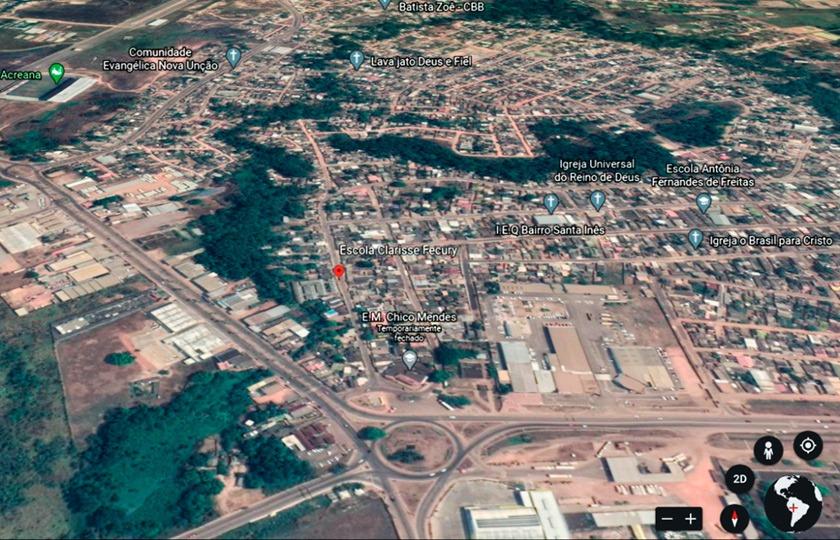 Imagem aérea do entorno escolar com quarteirões e quadras próximas à escola. Há galpões e áreas arborizadas ao redor. Fim da descrição.