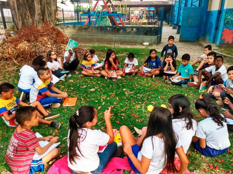 Em espaço externo com gramado, estudantes conversam sentados em círculo no chão. Fim da descrição.