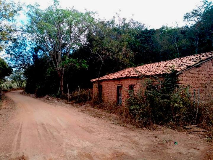 À direita, casa de tijolinhos na comunidade Conceição. À esquerda, estrada de terra. Ao lado e ao fundo da casa, área de mata. Fim da descrição.