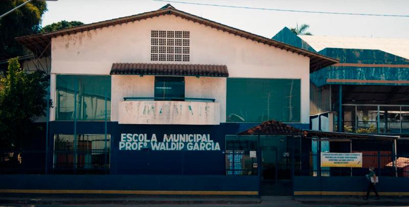 Fachada da Escola Municipal Prof Waldir Garcia, que possui muro e portões azuis. Fim da descrição.