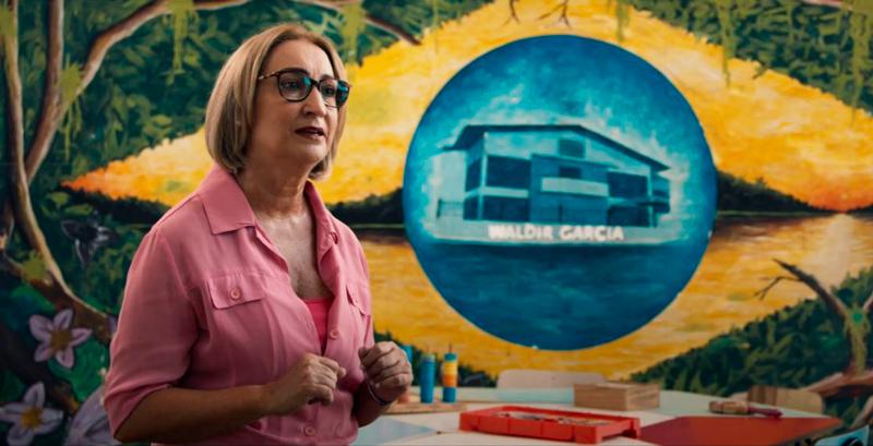 Lucia Cristina, de blusa rosa e óculos com armação preta, fala sobre escola. Ao fundo, parede ilustrada com bandeira do Brasil e fachada de escola ao centro. Fim da descrição.