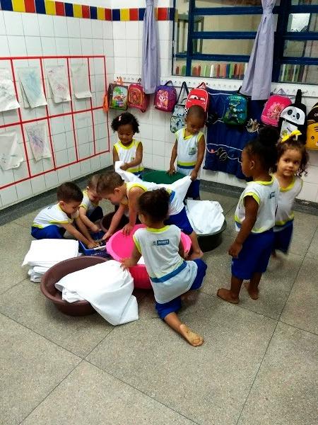 Em sala de aula, oito crianças brincam com bacias e lençóis brancos. Fim da descrição.