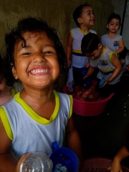 Em sala de aula, criança sorri para câmera, enquanto três crianças ao fundo brincam com bacia de água. Fim da descrição.