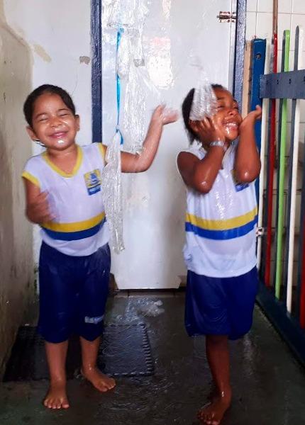 Em sala de aula, duas crianças molhadas brincam com saquinhos com água suspensos no teto. Fim da descrição.
