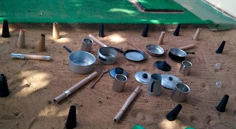 Panelas de alumínio espalhadas Em chão de areia. Fim da descrição.