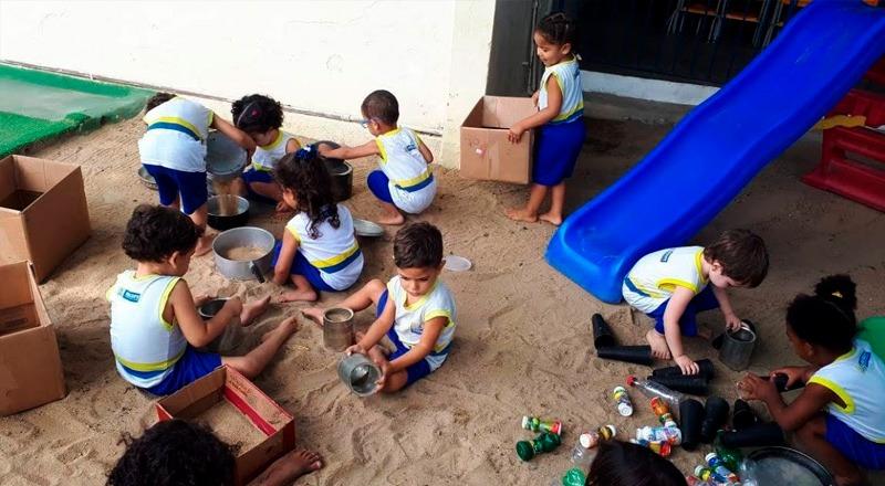 Em chão de areia. nove crianças brincam com panelas e caixas de papelão. Fim da descrição.