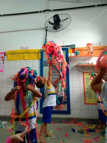 Em sala de aula, três crianças uniformizadas brincam com fitas de papel colorido. Duas deles estão com as fitas em suas cabeças, enquanto outra joga o objeto para cima. Fim da descrição