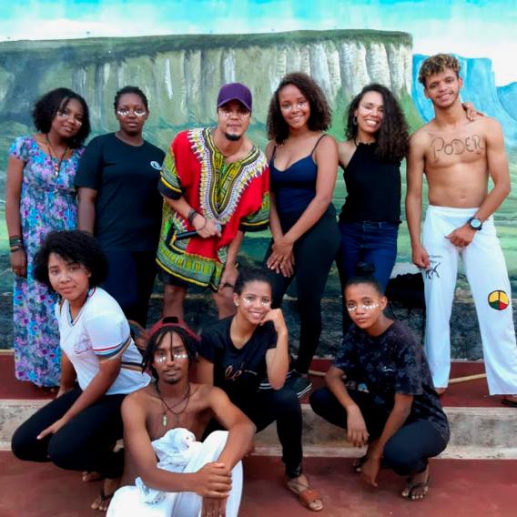 Estudantes caracterizados para musical de cultura afro-brasileira posam para foto ao lado da educadora Maria Isabel. Fim da descrição.